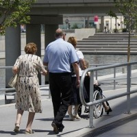 A disabled woman being wheeled down a ramp